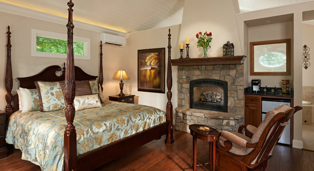 Charming guest room with four poster bed, wood floors, stone fireplace, rocking chair and ceiling fan