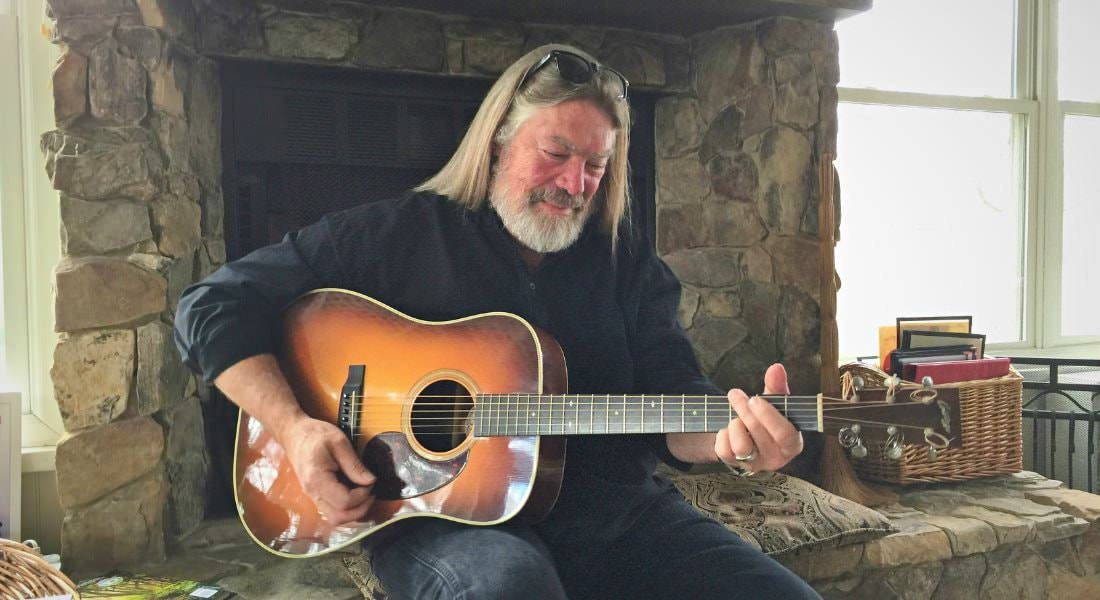 Man with long gray hair and beard sitting in front of a stone fireplace playing an acoustic guitar
