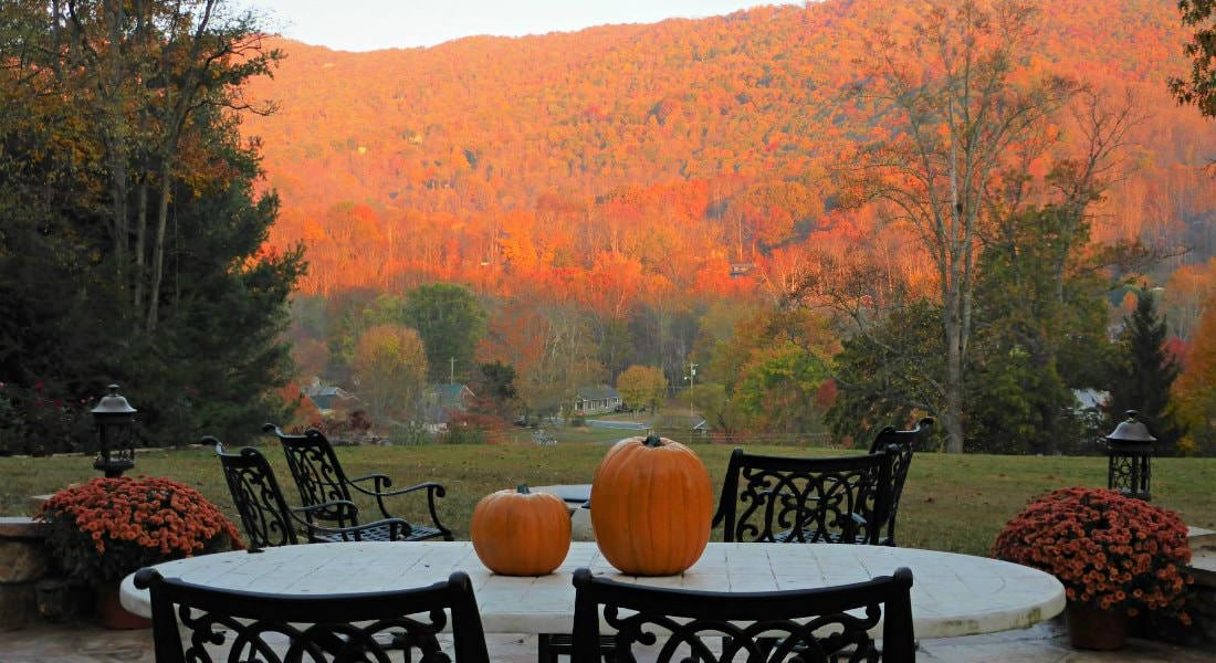 Patio chairs, round table topped with orange pumpkins, and view of the mountains in red and green during the fall
