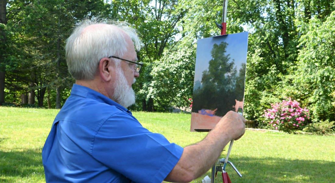Gray haired man with beard sitting outside amidst green grass and trees, painting a landscape