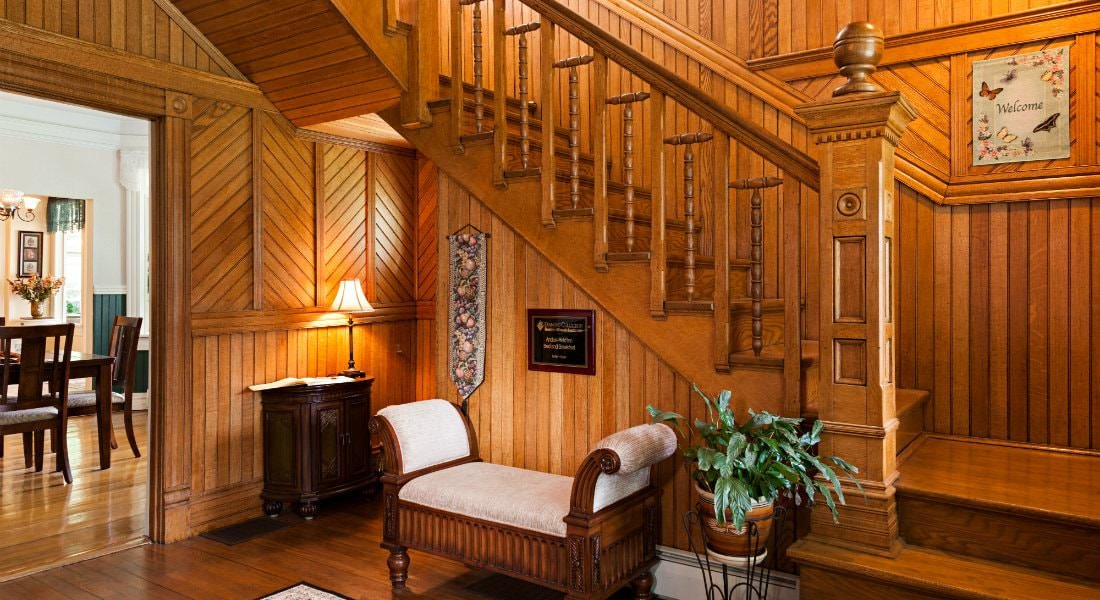 Foyer entry with wood paneled walls, wood floors, and a bench and green plant under -shaped stairs