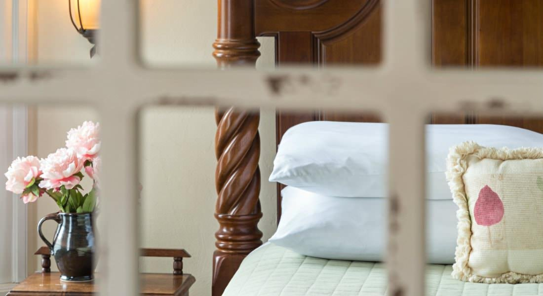 Close up view of guest bed with wood headboard, light green bedding, several pillows, and night stand with fresh flowers