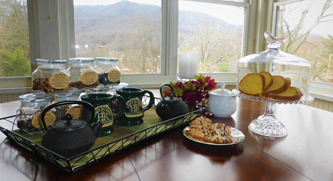 Table topped with teapot, mugs, tea, fresh flowers, and sliced cake, all amidst mountain-views through several windows