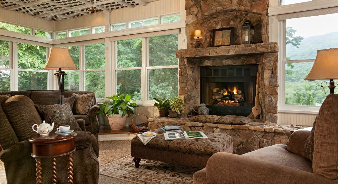 Spacious sun room with stone fireplace, tall windows, upholstered furniture and landscape views