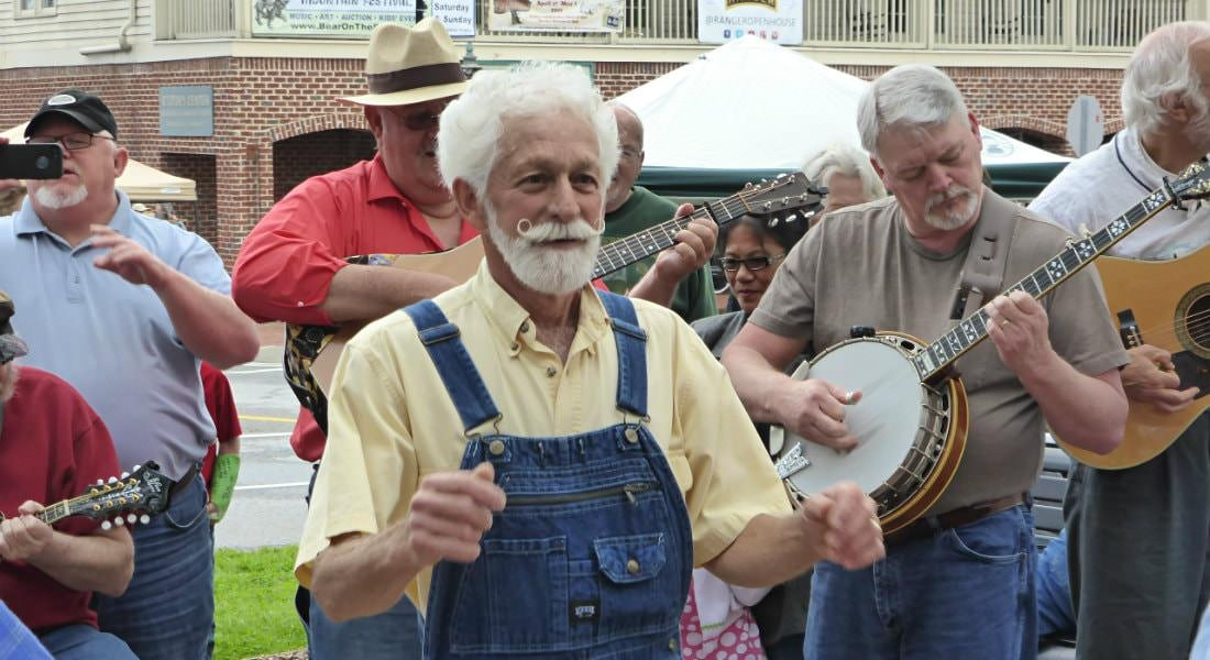 Several people outside with banjos and guitars, clapping, dancing and smiling