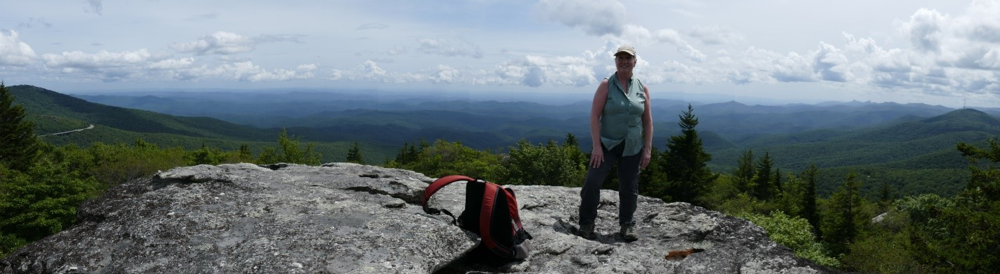 Andrea standing on top of black rock with a panoramic view of mountains in the background.