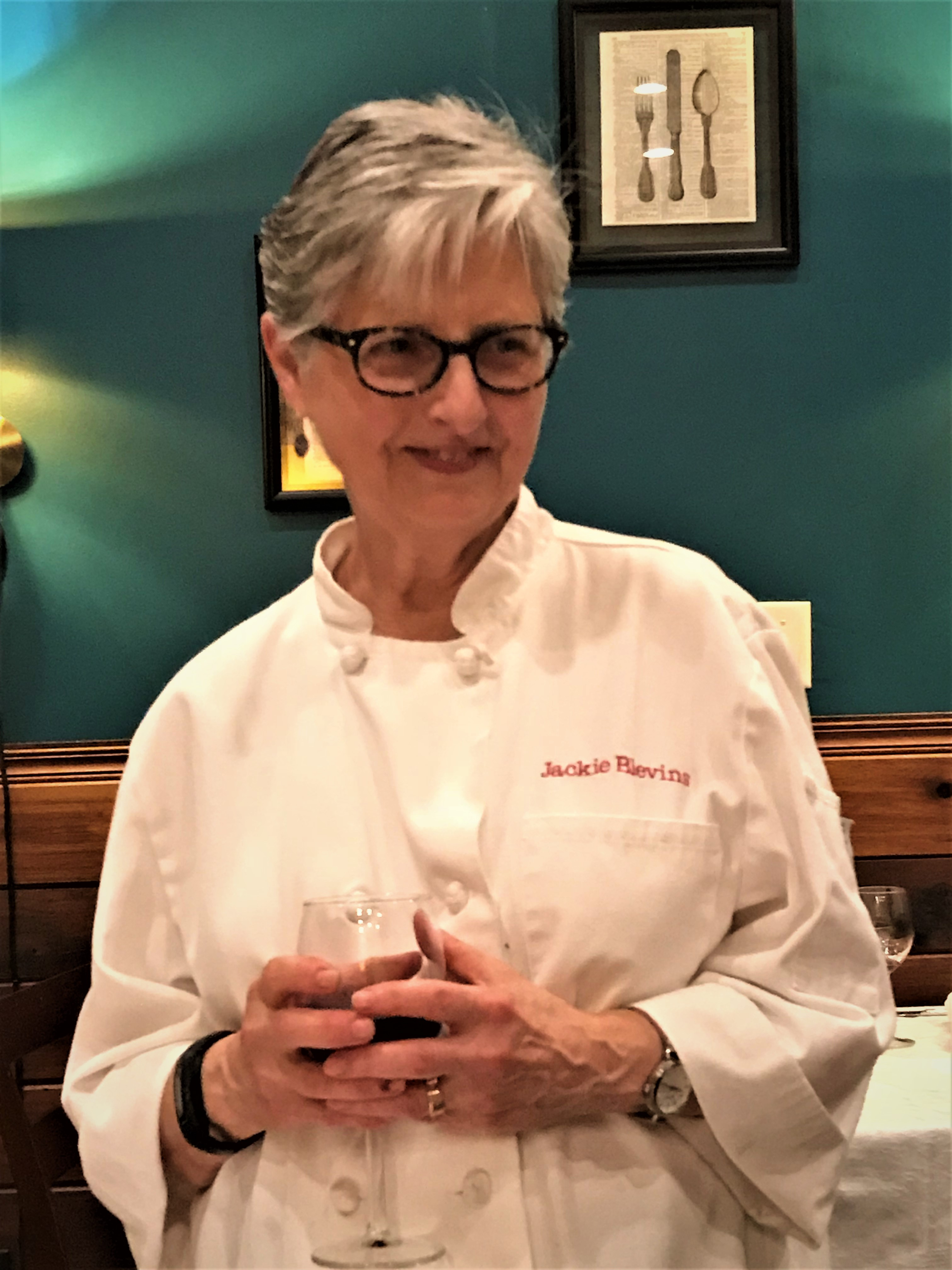 Chef Jackie Blevins in her chef's jacket enjoying a glass of wine