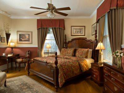 Beige guest room with ceiling fan, wood four poster bed, elegant furnishings, wood floors, and two windows