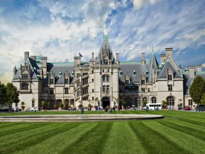 Grand French chateau style Biltmore mansion, several steep roof peaks, huge green front lawn, blue skies with white clouds