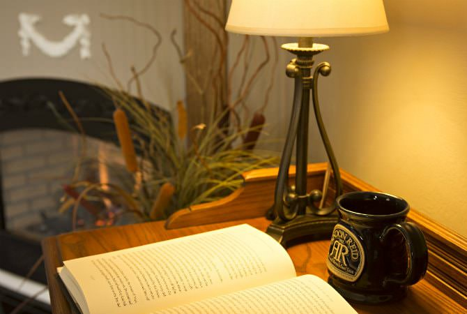 Close up view of an open book on a desk with a lamp and Andon Reid coffee mug