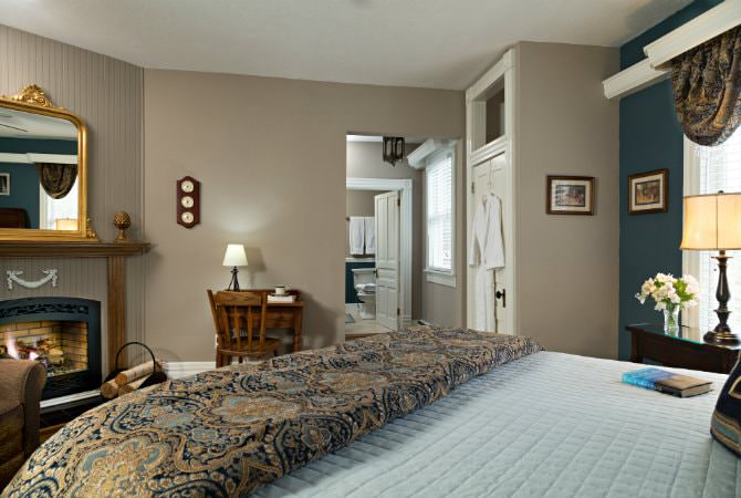 Tan and blue guest room, large bed with brown and blue bedding, natural light, and bathroom in the background