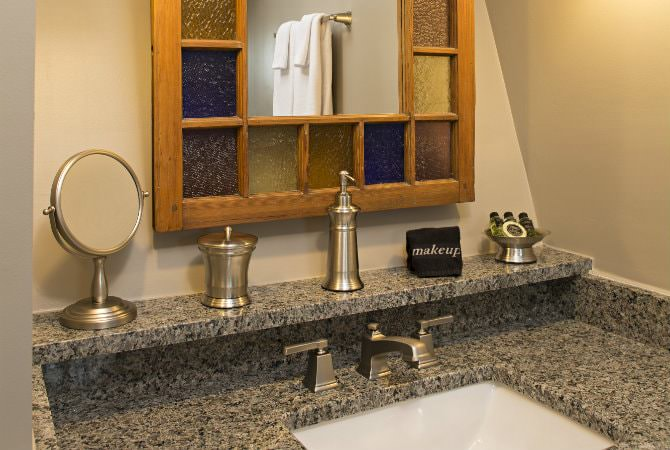 Stone vanity top with drop-in sink and ledge containing mirror, soap and toiletries with a stained-glass-framed mirror