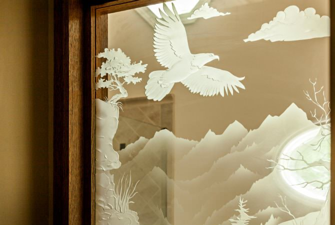 Door with glass window etched in white with pictures of a flying bird, clouds, mountains and trees