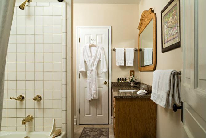 Beige bathroom, vanity with drop-in sink and mirror, tiled tub/shower, white robe and towels