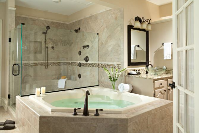 Beige bathroom with large tiled walk-in shower, large soaking tub, and vanity with vessel bowl sink