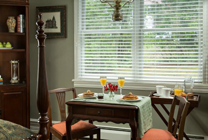 Light green room with double window and small table with two chairs set for breakfast with pancakes and orange juice