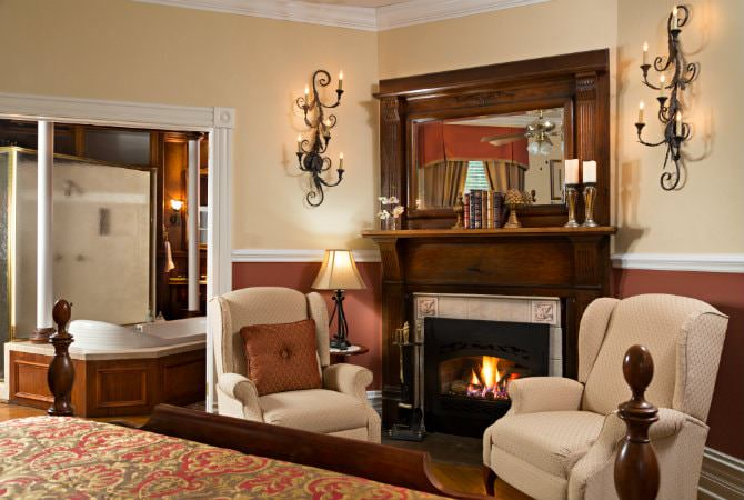 Tan and rust guest room with two beige chairs flanking a fireplace and scrolled sconce lighting