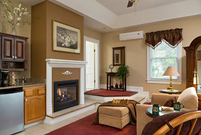 Beautiful tan living room with natural light, fireplace, beverage center, upholstered furniture and floor rugs