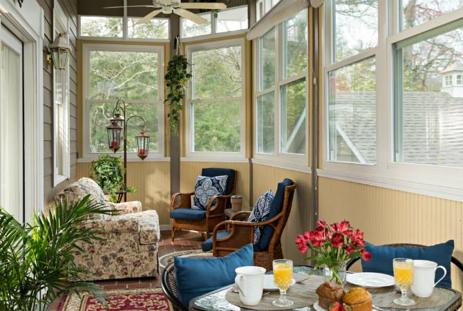 Creamy yellow sunroom with lots of windows, ceiling fans, upholstered furniture and dining table and chairs