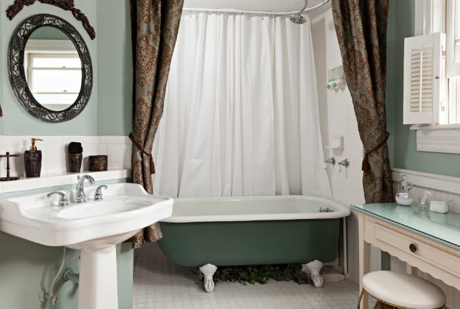 Sage green bathroom with clawfoot tub, white pedastal sink, window with shutters and tile floors