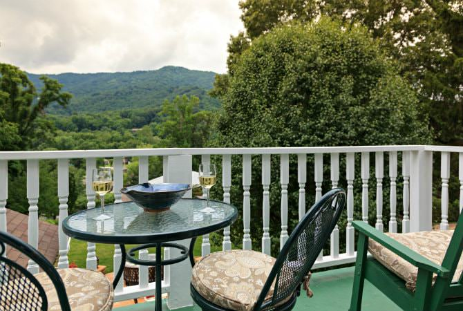 Balcony with white railing, tables and chairs with cushions, and an overlook of lush green trees and mountains