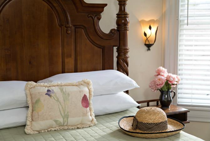 Comfortable bed with tall wood headboard, light green bedding and white pillows, sconce lighting, and natural light