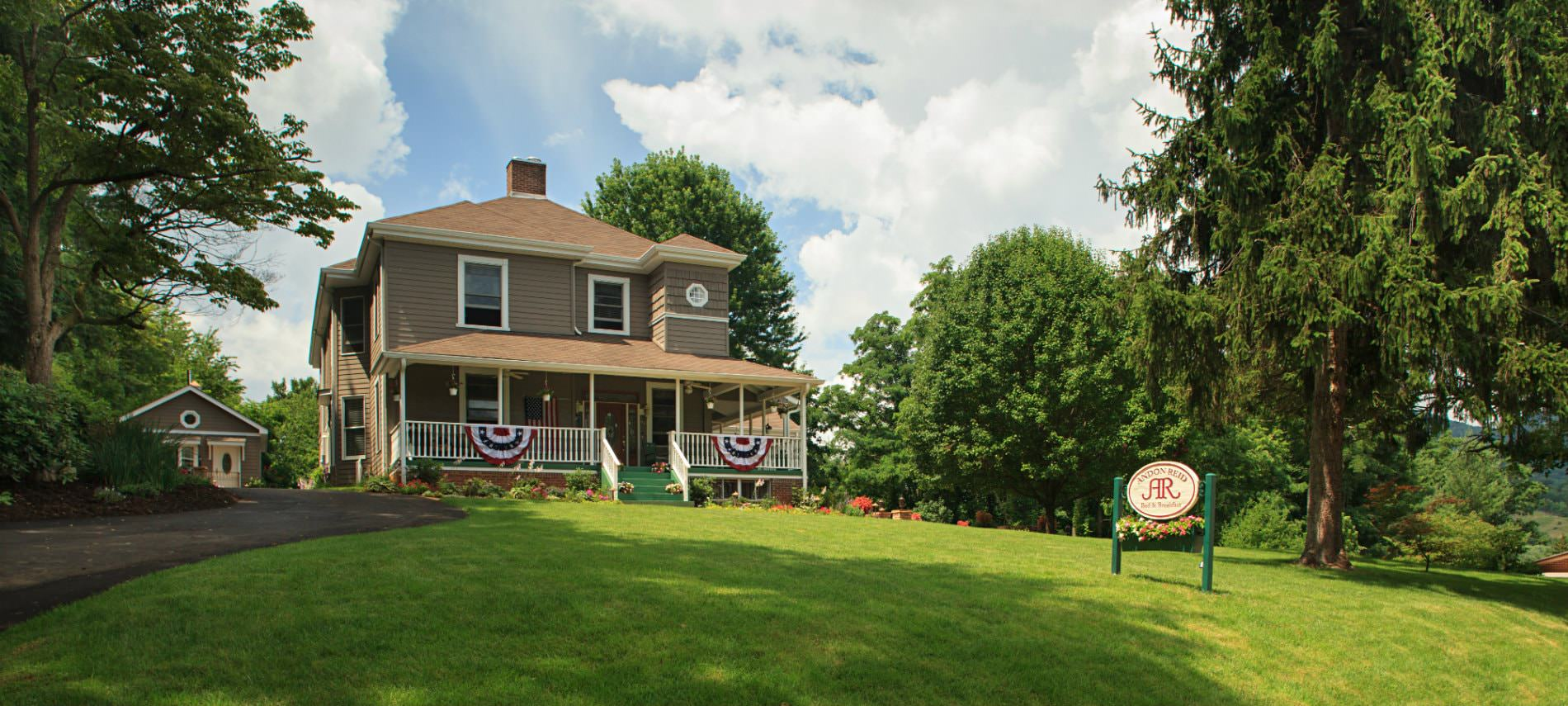 Brown sided two story home with white trim, hip roof, surrounded by green grass, lush green trees and blue skies