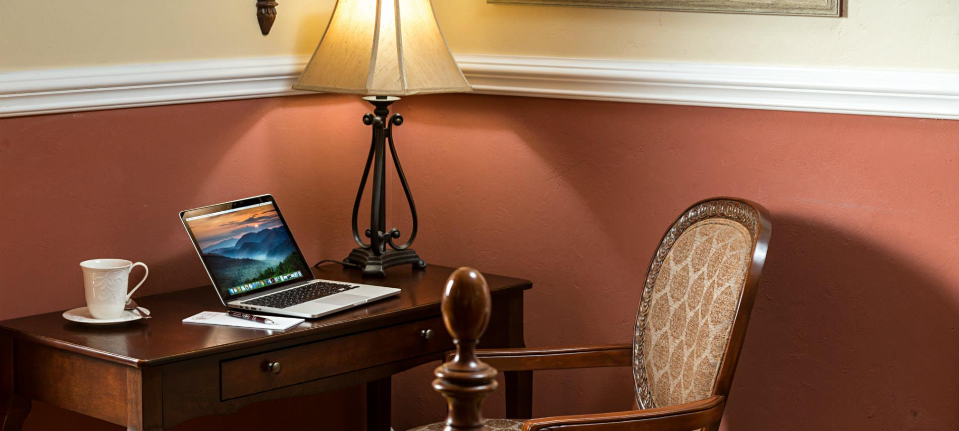Terracotta and cream room, small wood desk and chair in the corner with laptop and white cup and saucer