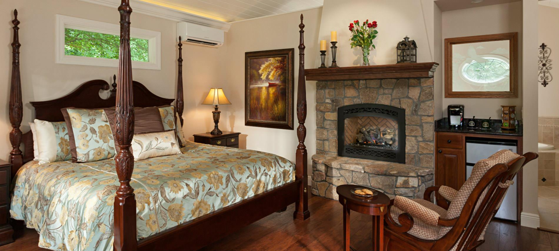 Elegant beige guest room with wood floors, stone fireplace, elegant four poster bed, beverage center and rocking chair
