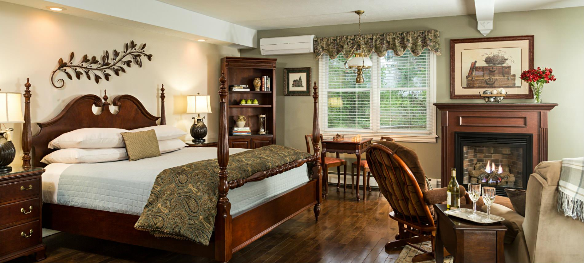 Beige and sage room, wood floors, four poster bed with matching night stands, sitting area with fireplace and double window