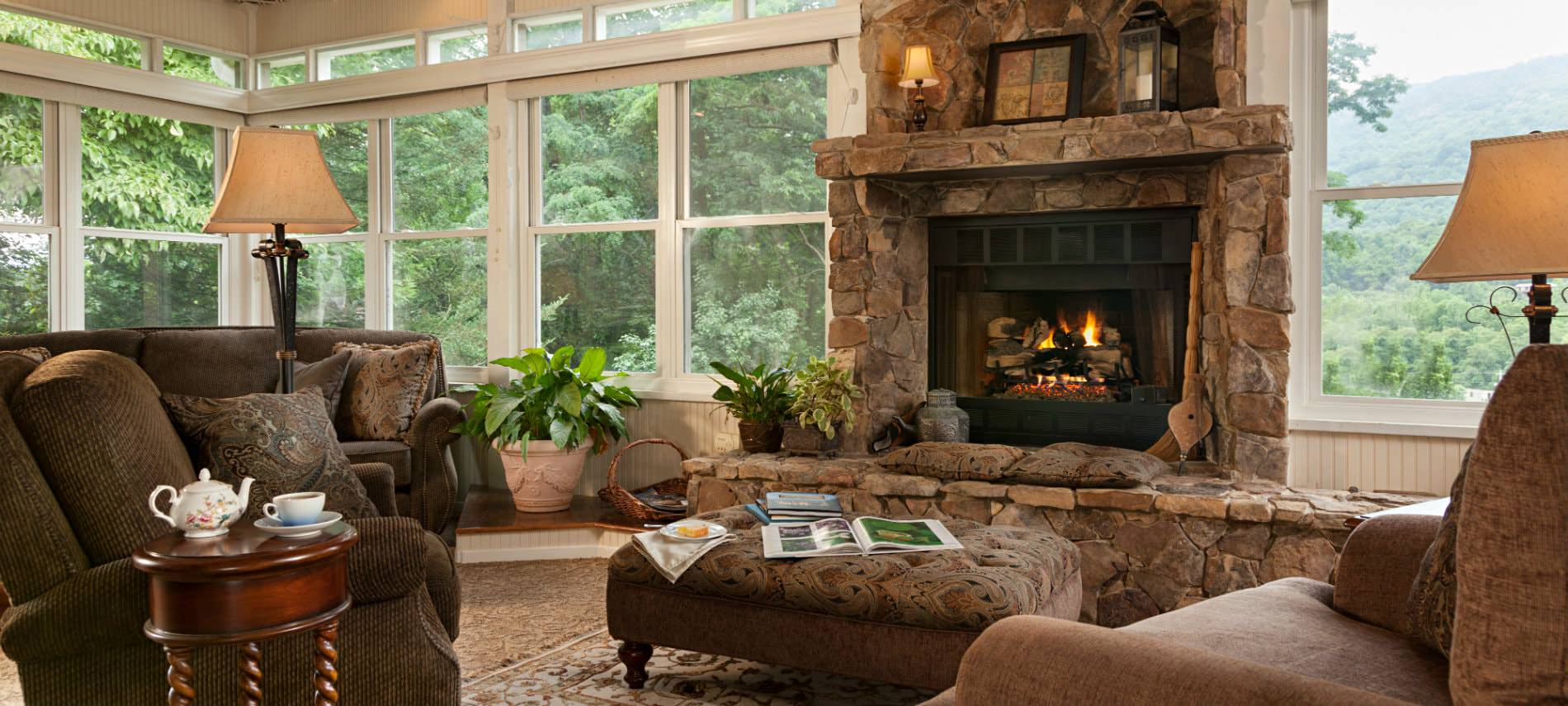 Beautiful sun room surrounded with windows, large stone hearth and fireplace, upholstered furniture and lush green views