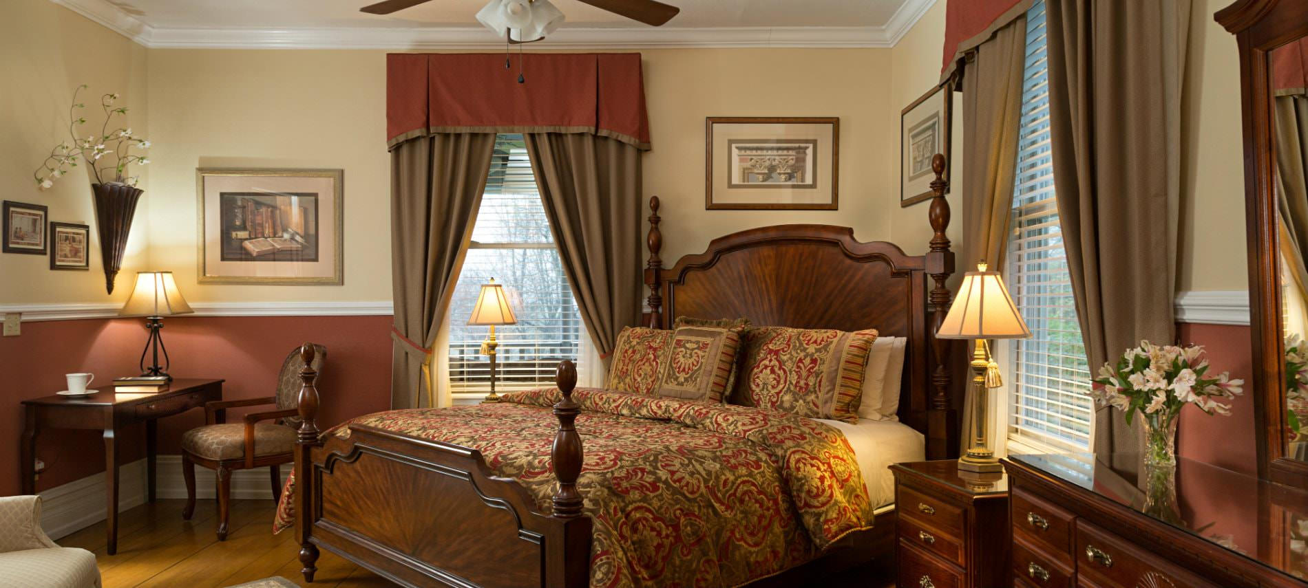 Creamy beige and rust red room with wood floors, elegant four poster bed, desk and chair and natural light
