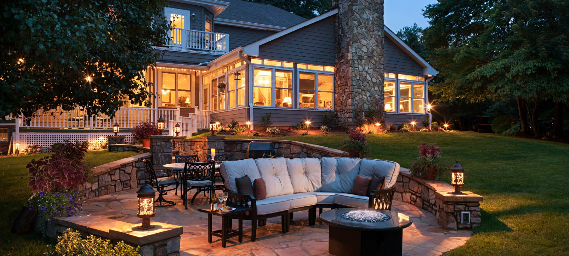 Sunken stone patio with firepit, comfy outdoor furniture, beautiful landscaping, and view of inn with all the lights on