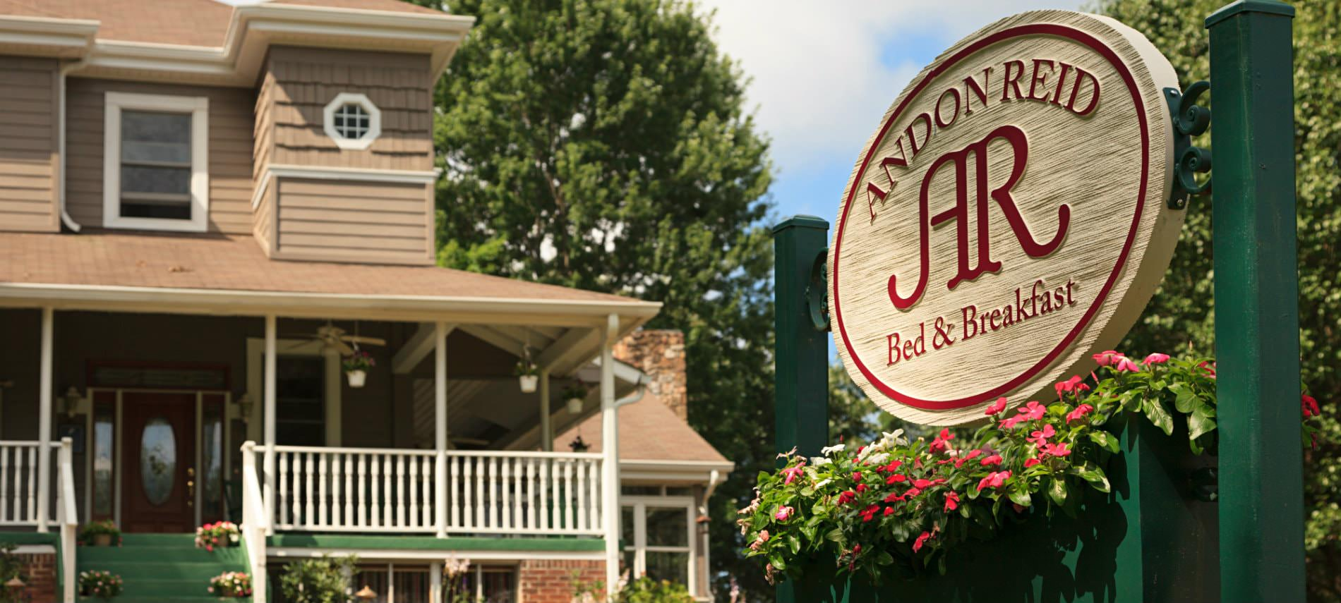 Andon Reid Bed & Breakfast sign hanging on green post with pink flowers, view of brown sided B&B in the background