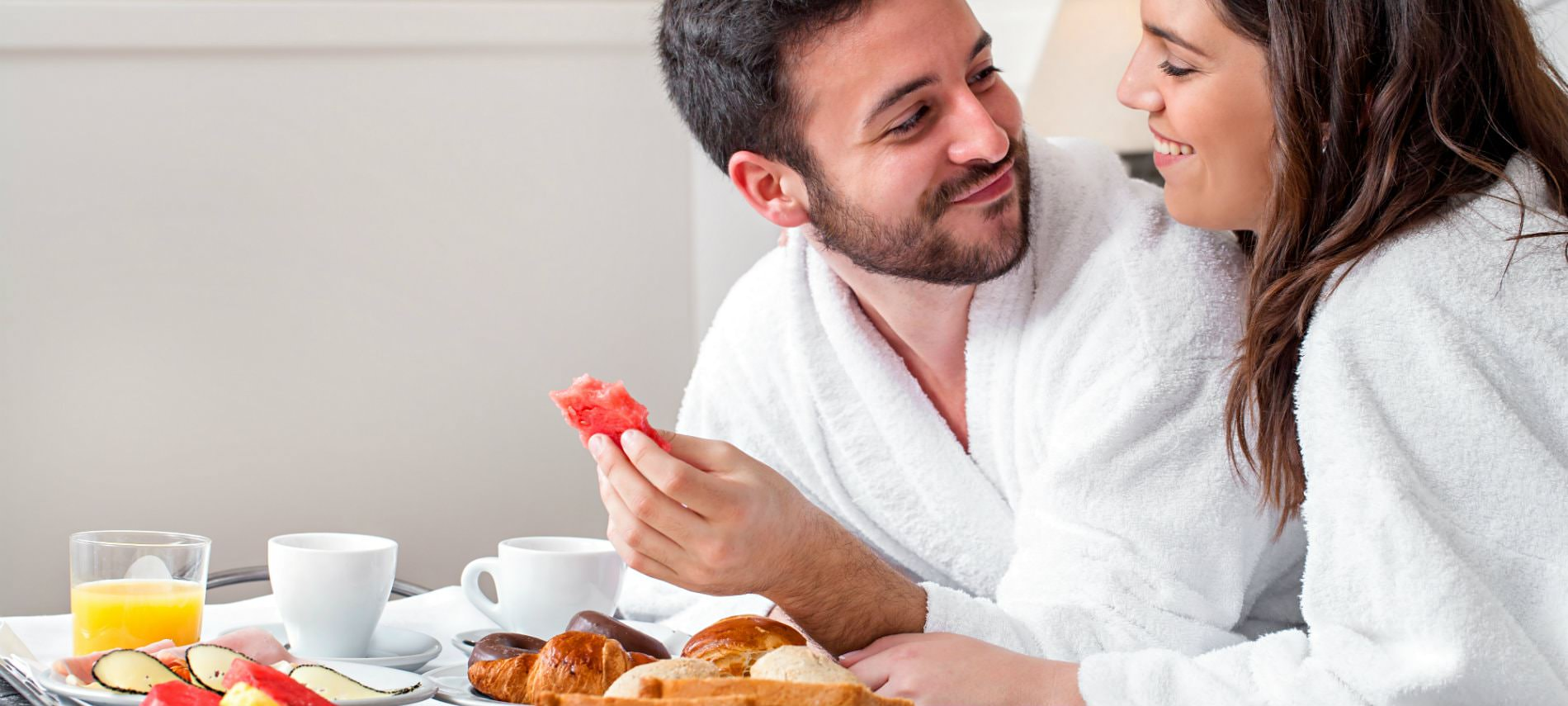 Brown haired man and woman smiling, wearing white terry robes, eating breakfast