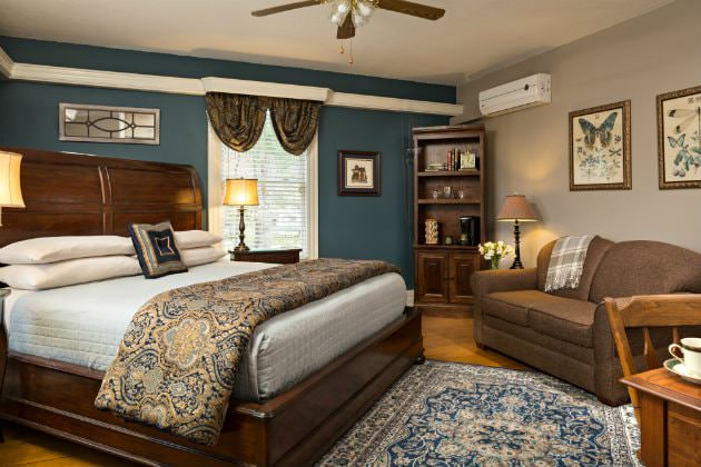 Elegant beige and navy room with wood floors, wood sleigh bed with blue and gold bedding, loveseat and window