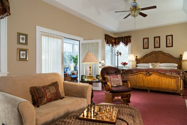 Spacious beige guest room, red carpeting, large wood bed, sitting area, natural light, French door to a cheery sunroom