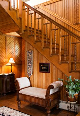 Wood paneled room, open L-shaped stairway with wood railing, and upholstered bench under the stairs