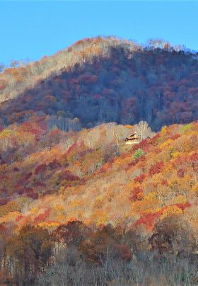 Mountain view with fading colored trees in red, orange and brown amidst blue skies