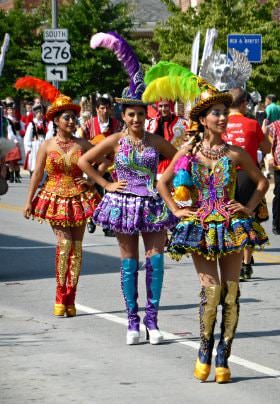 Parade with several women walking down the road wearing brightly colored costumes