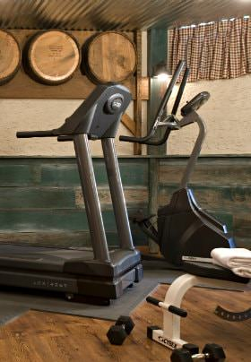 Exercise room with treadmill and stairstepper, wood floors and green horizontal beadboard