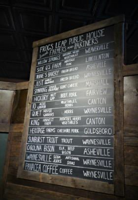 Large chalkboard with menu options written in white chalk and rustic wood frame