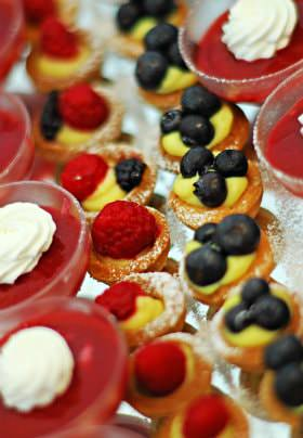 Rows of cups filled with red dessert and white whipped cream, and mini baked dessert cups topped with fresh fruit
