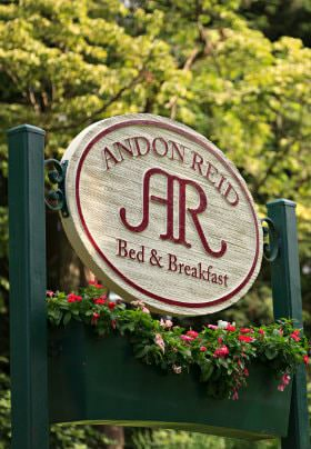 Green sign with flowerbox, colorful flowers and white oval sign with Andon Reid Bed & Breakfast in red lettering