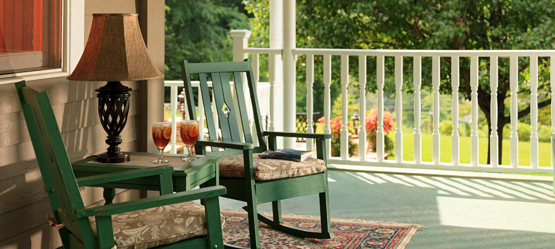Covered porch with green rocking chairs, light green painting floor, white spindle railing, surrounded by green landscaping