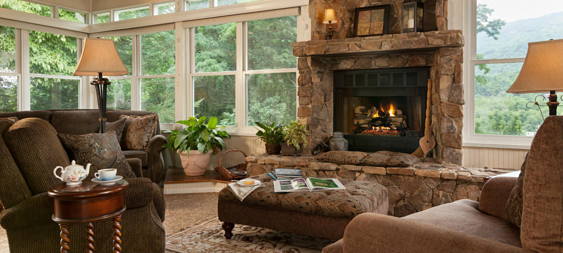 Beautiful and cozy sunroom with tall windows, stone fireplace, upholstered furniture
