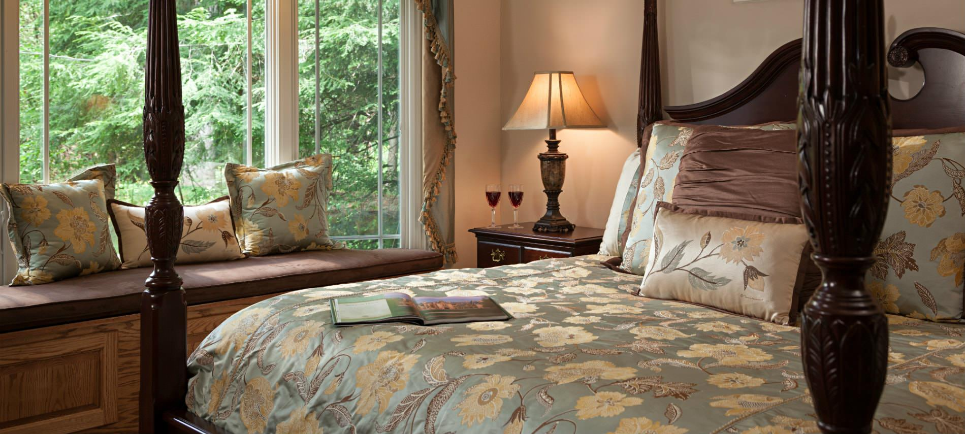 Elegant guest room, four poster bed with light blue and cream bedding, large window with window seat