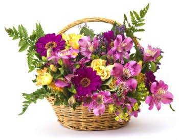 Tan wicker flower basket with handle filled with pink, violet and yellow flower with green leafy stems