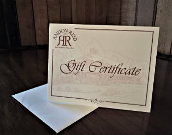 White card propped up on a table with Andon Reid Gift Certificate in red scrolly lettering
