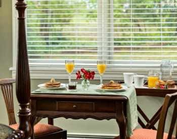 Small wood table with two chairs set for breakfast with pancakes and orange juice in front of double window